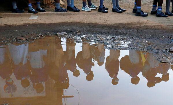 Силуэты школьников, стоящих в очереди в трущобах Кибера в Найроби - Sputnik Азербайджан