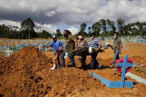 Сыновья 73-летней Вероники Феррейра, скончавшейся от COVID-19, на ее похоронах на кладбище Parque Taruma в Манаусе, Бразилия - Sputnik Азербайджан