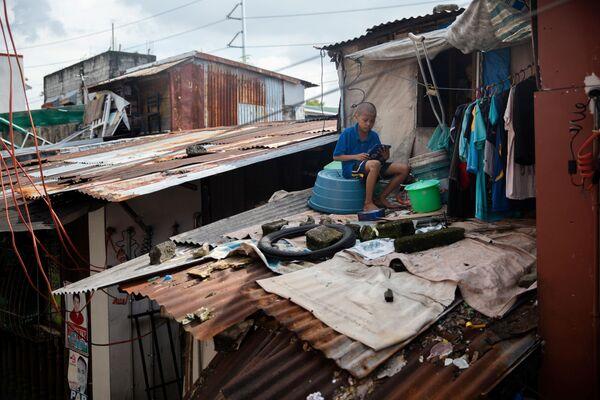 Ученик 5-го класса 10-летний Джей Ар Кальма на крыше своего дома во время онлайн-уроков Манила, Филиппины - Sputnik Азербайджан