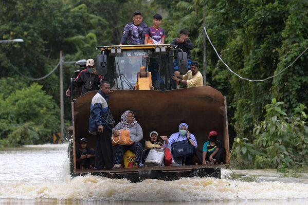 Жители едут на экскаваторе через паводковые воды после сильного муссонного ливня в Ланьчанге, Малайзия - Sputnik Азербайджан