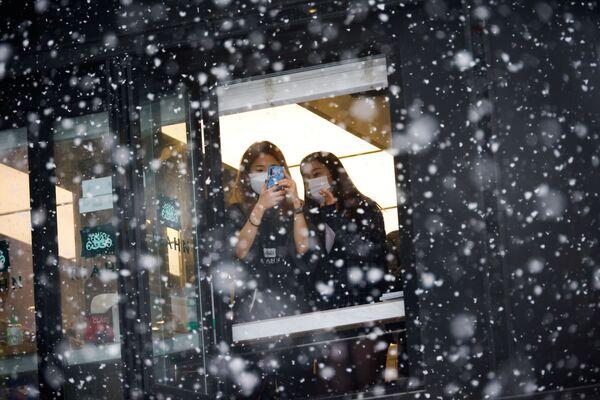 Девушки фотографируют снегопад в Сеуле  - Sputnik Азербайджан