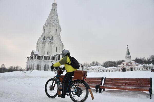 Молодой человек на велосипеде около церковки Вознесения Господня в парке Коломенское в Москве - Sputnik Азербайджан
