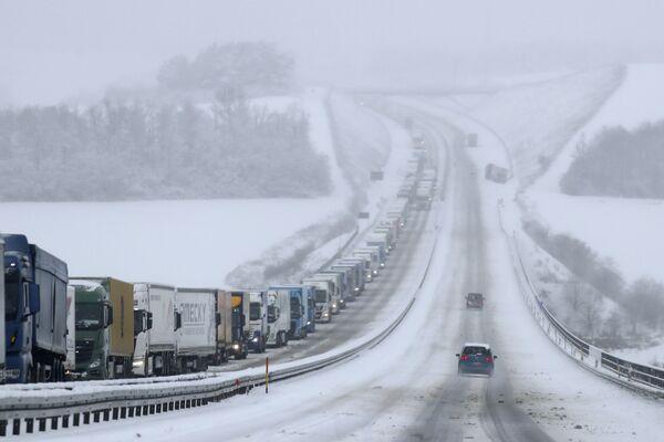 Грузовики на трассе во время снегопада в Германии - Sputnik Азербайджан