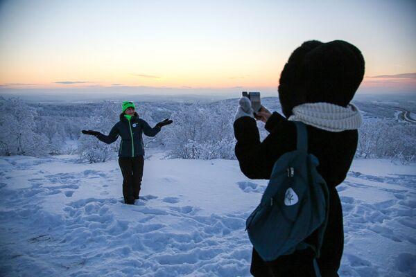 Девушка фотографируется во время встречи первого рассвета после полярной ночи на горе Солнечная в Мурманске - Sputnik Азербайджан