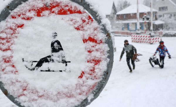 People carrying sledges walk past a snow covered traffic sign, as the spread of the coronavirus disease (COVID-19) continues, in Zurich, Switzerland January 12, 2021.  - Sputnik Азербайджан