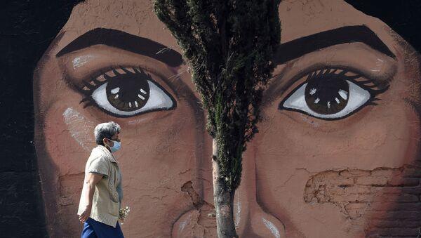 Женщина  проходит мимо граффити на одной из стен кладбища San Nicolas Tolentino в муниципалитете Истапалапа в Мехико - Sputnik Azərbaycan