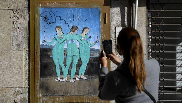 Женщина фотографирует на свой мобильный телефон новую работу итальянского уличного художника TvBoy под названием «Три вакцины», на которой изображена картина итальянского художника Рафаэля «Три грации», в Барселоне, 19 января 2021 года - Sputnik Азербайджан