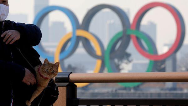 Мужчина с котом в сумке на фоне олимпийских колец в Токио - Sputnik Азербайджан