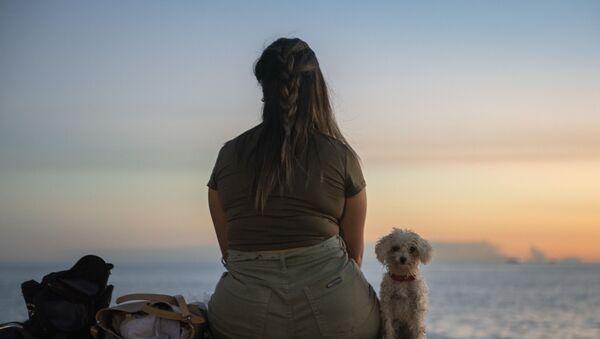 Женщина и ее собака сидят на дамбе на закате, фото из архива - Sputnik Azərbaycan