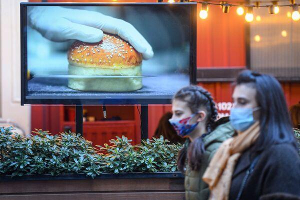 Прохожие перед рекламным баннером на улице в Баку, 1 февраля 2021 года - Sputnik Azərbaycan