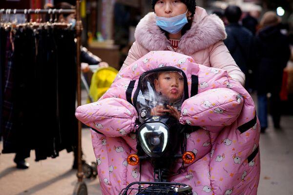 Женщина везет ребенка в коляске на улице в Ухане - Sputnik Азербайджан