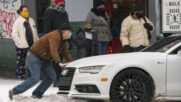 Мужчина толкает автомобиль на заснеженной улице в Сиэтле, штат Вашингтон  - Sputnik Азербайджан