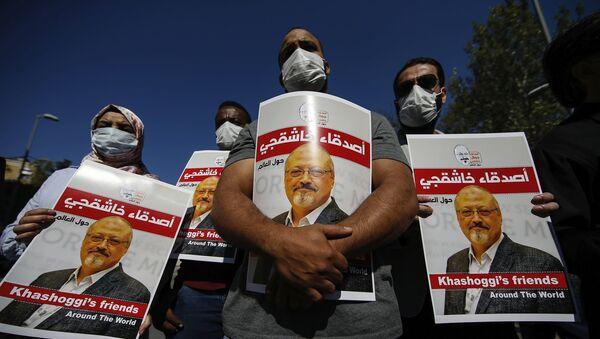 Люди держат плакаты с изображением убитого саудовского журналиста Джамаля Кашогги,фото из архива - Sputnik Азербайджан