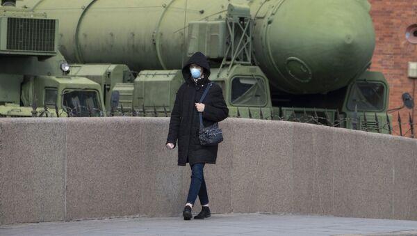 Женщина в маске проходит мимо российской межконтинентальной пусковой установки баллистических ракет «Тополь М», фото из архива - Sputnik Азербайджан