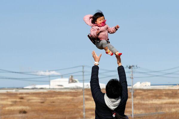 Потерявший родных во время землетрясения 2011 года отец с ребенком в префектуре Фукусима  - Sputnik Азербайджан