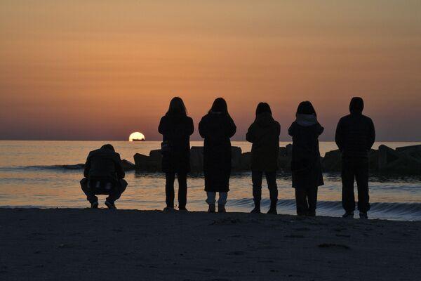 Люди во время молитвы о жертвах землетрясения 2011 года в Японии  - Sputnik Азербайджан