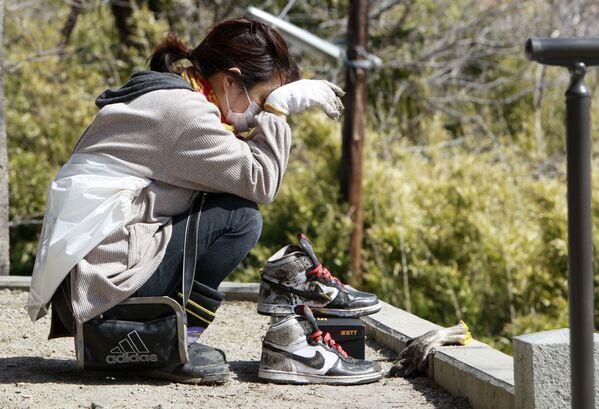 Девушка во время отдыха после очистки дома от обломков в Японии  - Sputnik Азербайджан