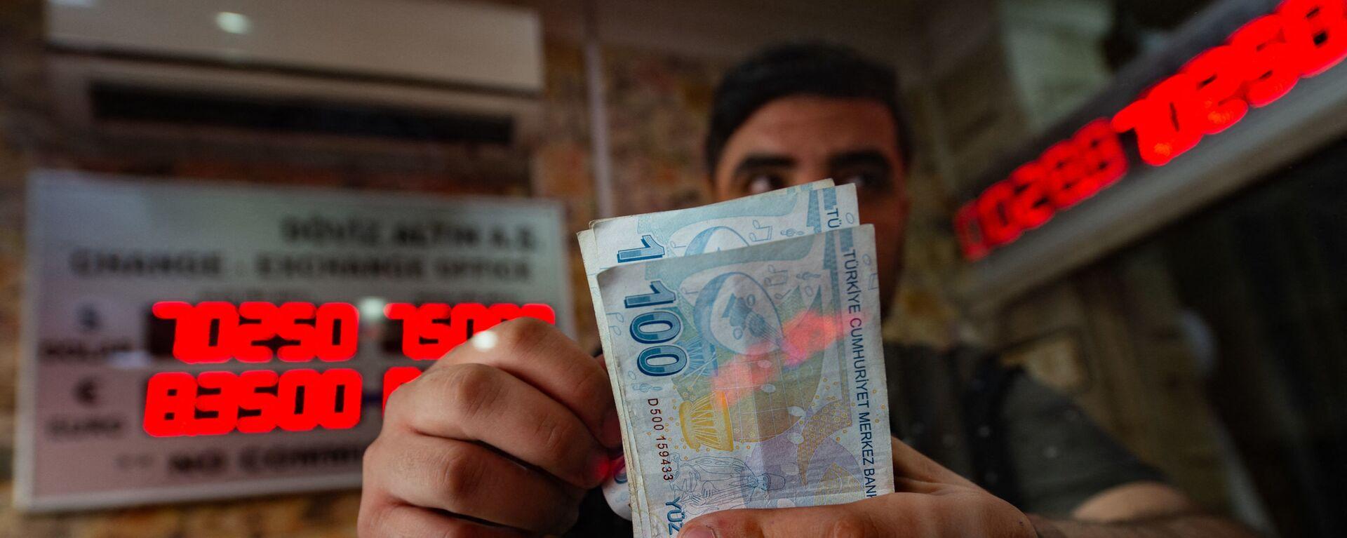 Сотрудник пункта обмена валюты считает банкноты турецких лир, фото из архива - Sputnik Азербайджан, 1920, 02.04.2021
