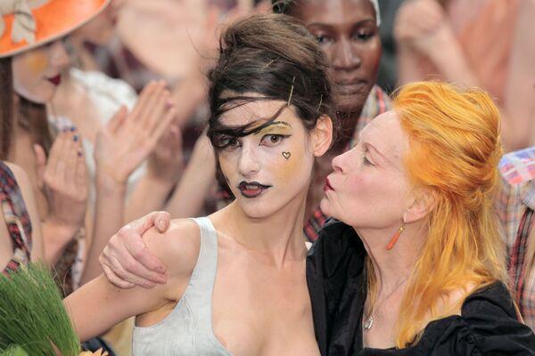 Британский модельер Вивьен Вествуд целует модель после окончания модного показа ее коллекции prêt-à-porter весна-лето 2011 в Париже - Sputnik Азербайджан