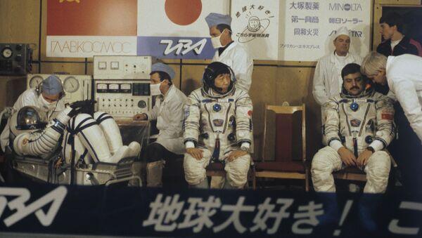 Экипаж космического корабля Союз ТМ-11 - командир корабля Виктор Афанасьев, японский журналист Тоехиро Акияма и летчик-космонавт СССР Муса Манаров (слева направо) во время подготовки к старту. Космодром Байконур - Sputnik Азербайджан