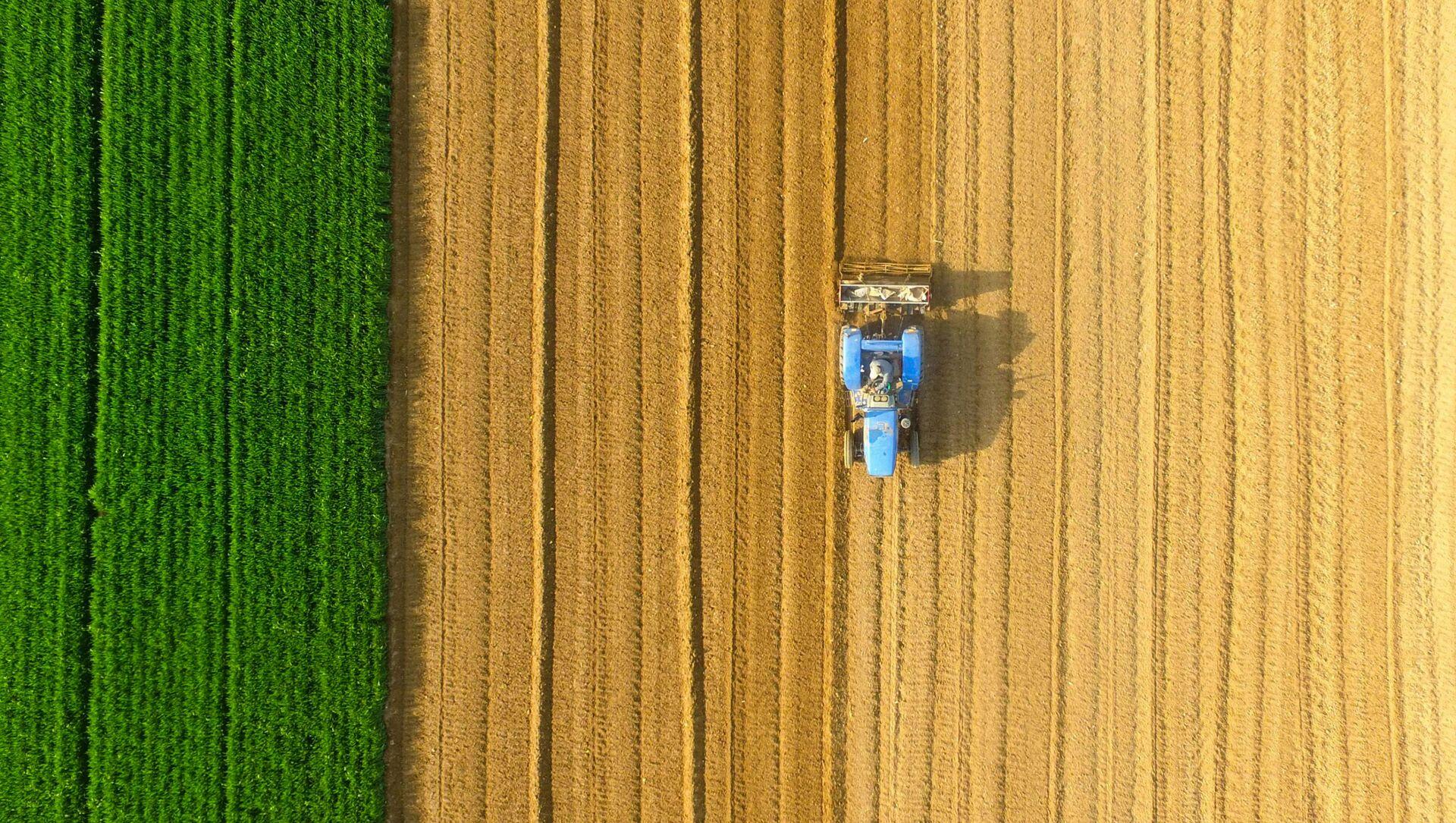 Трактор обрабатывает землю, фото из архива  - Sputnik Azərbaycan, 1920, 30.08.2021