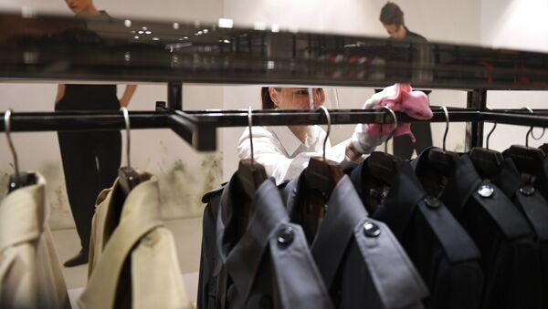 Продавец протирает вешалку в магазине одежды - Sputnik Азербайджан