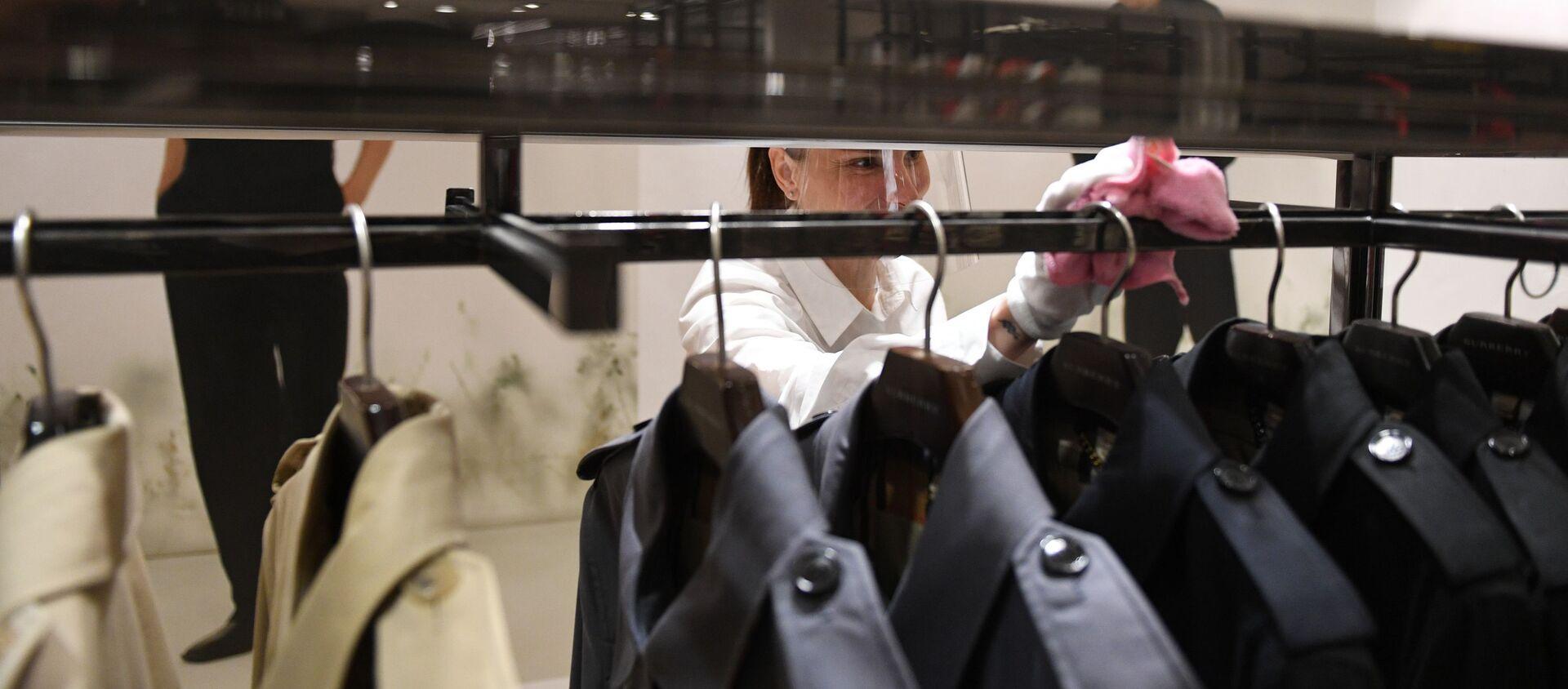 Продавец протирает вешалку в магазине одежды - Sputnik Азербайджан, 1920, 23.04.2021