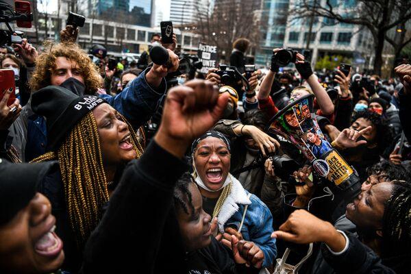 Люди празднуют оглашение приговора в суде над бывшим полицейским Дереком Човеном в Миннеаполисе, США - Sputnik Азербайджан