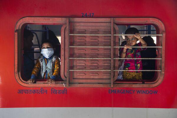 Мальчики смотрят в окно поезда на железнодорожной станции в Гаухати, Индия - Sputnik Азербайджан