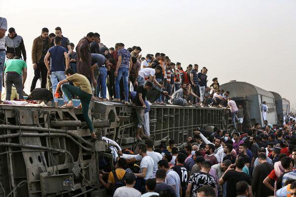Люди поднимаются на перевернутый вагон после аварии поезда в городе Тух, Египет - Sputnik Азербайджан