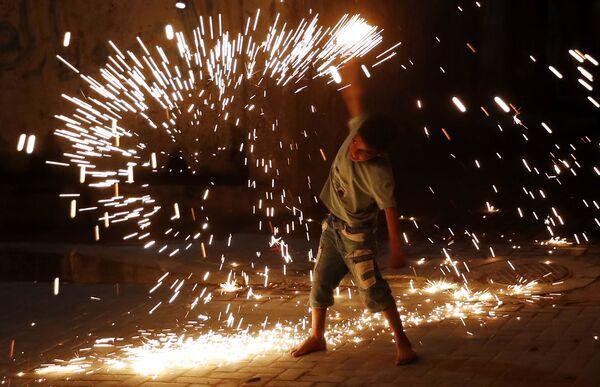Мальчик играет с фейерверком во время празднования месяца Рамадан в городе Газа - Sputnik Азербайджан