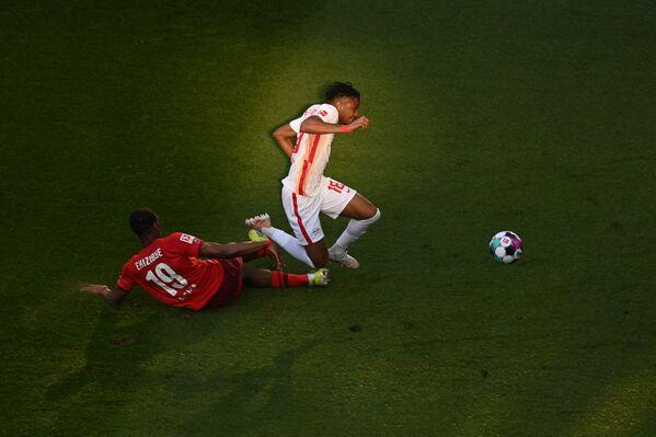 Голландский защитник Кельна Кингсли Эхизибу (слева) и французский полузащитник Лейпцига Кристофер Нкунку борются за мяч во время футбольного матча, Германия  - Sputnik Азербайджан