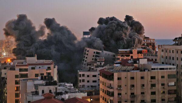 Пожарные тушат горящие многоквартирные дома после израильских авиаударов в городе Газа - Sputnik Азербайджан