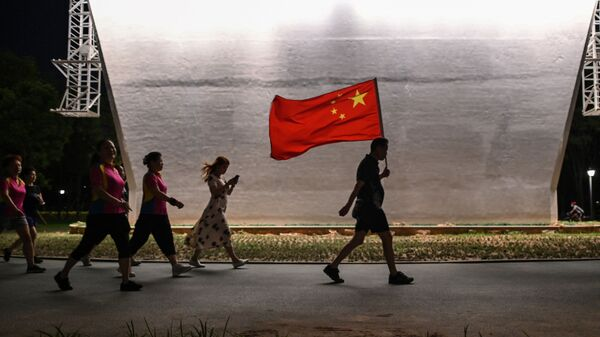 Мужчина с флагом Китая идет по парку, фото из архива - Sputnik Азербайджан