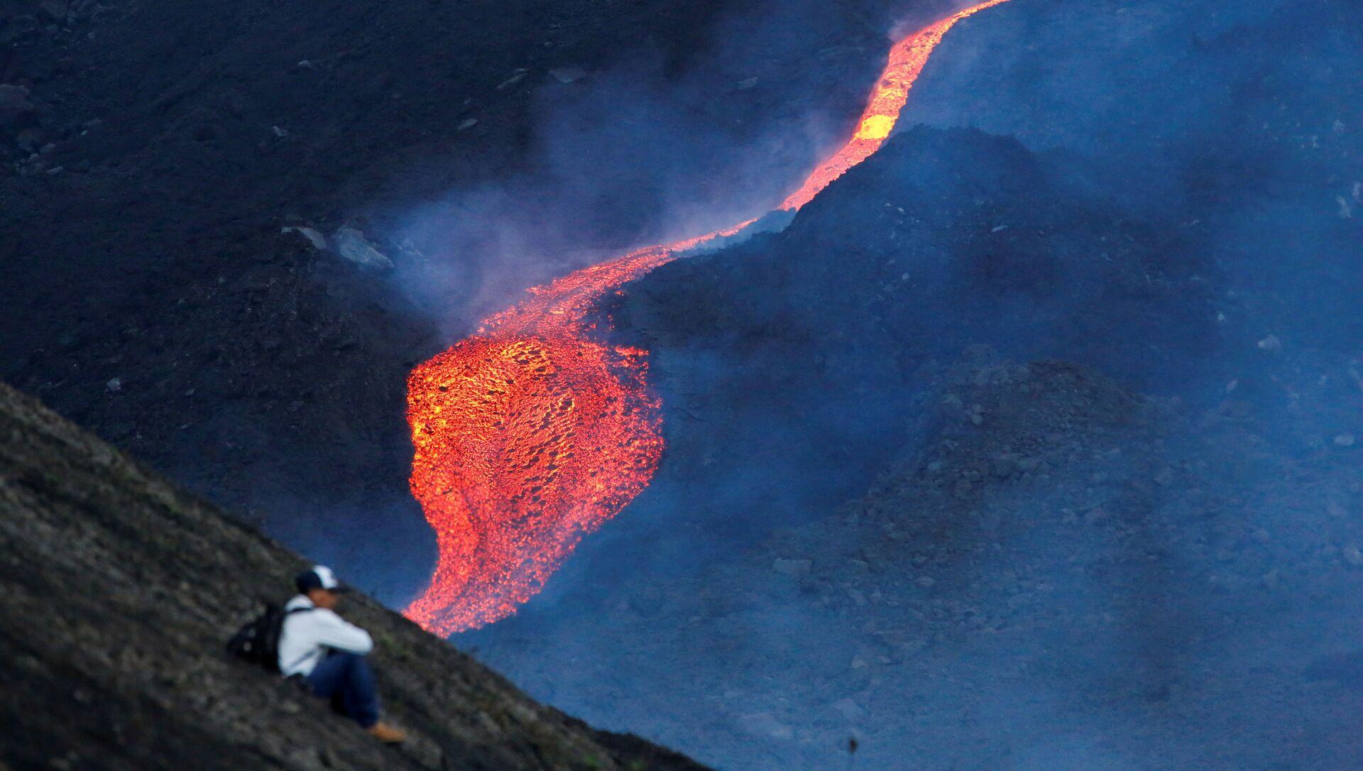 Мужчина наблюдает за течением раскаленной лавы вулкана Пакая в регионе Эскуинтла, Гватемала - Sputnik Азербайджан, 1920, 25.09.2021