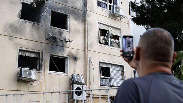 Израильтянин фотографирует поврежденный фасад здания в городе Ашкелон на юге Израиля, 11 мая 2021 года  - Sputnik Azərbaycan