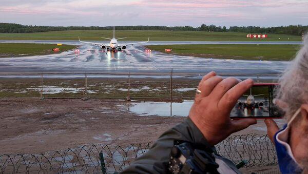 Женщина фотографирует посадку самолета авиакомпании Ryanair в Вильнюсе - Sputnik Азербайджан