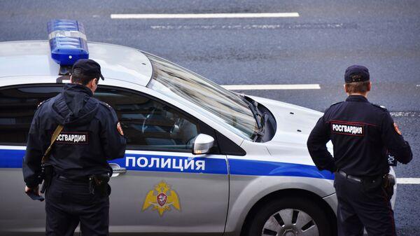 Сотрудники Росгвардии у полицейской машины - Sputnik Azərbaycan