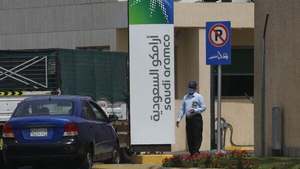 Сотрудник службы безопасности в маске проверяет автомобиль, въезжающий на территорию комплекса Saudi Aramco в Джидде, Саудовская Аравия, в понедельник, 9 марта 2020 года - Sputnik Азербайджан