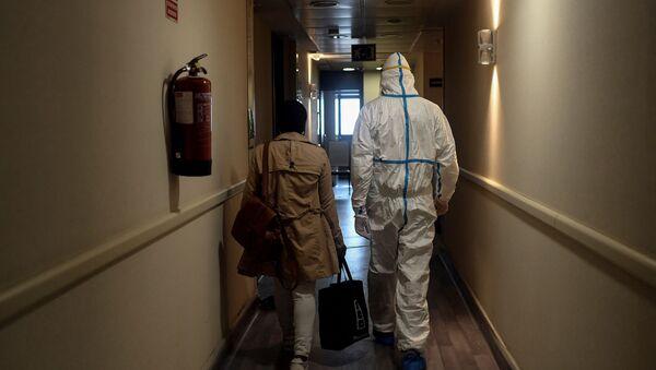 Медицинский работник сопровождает женщину в ее комнату в отеле, фото из архива - Sputnik Азербайджан