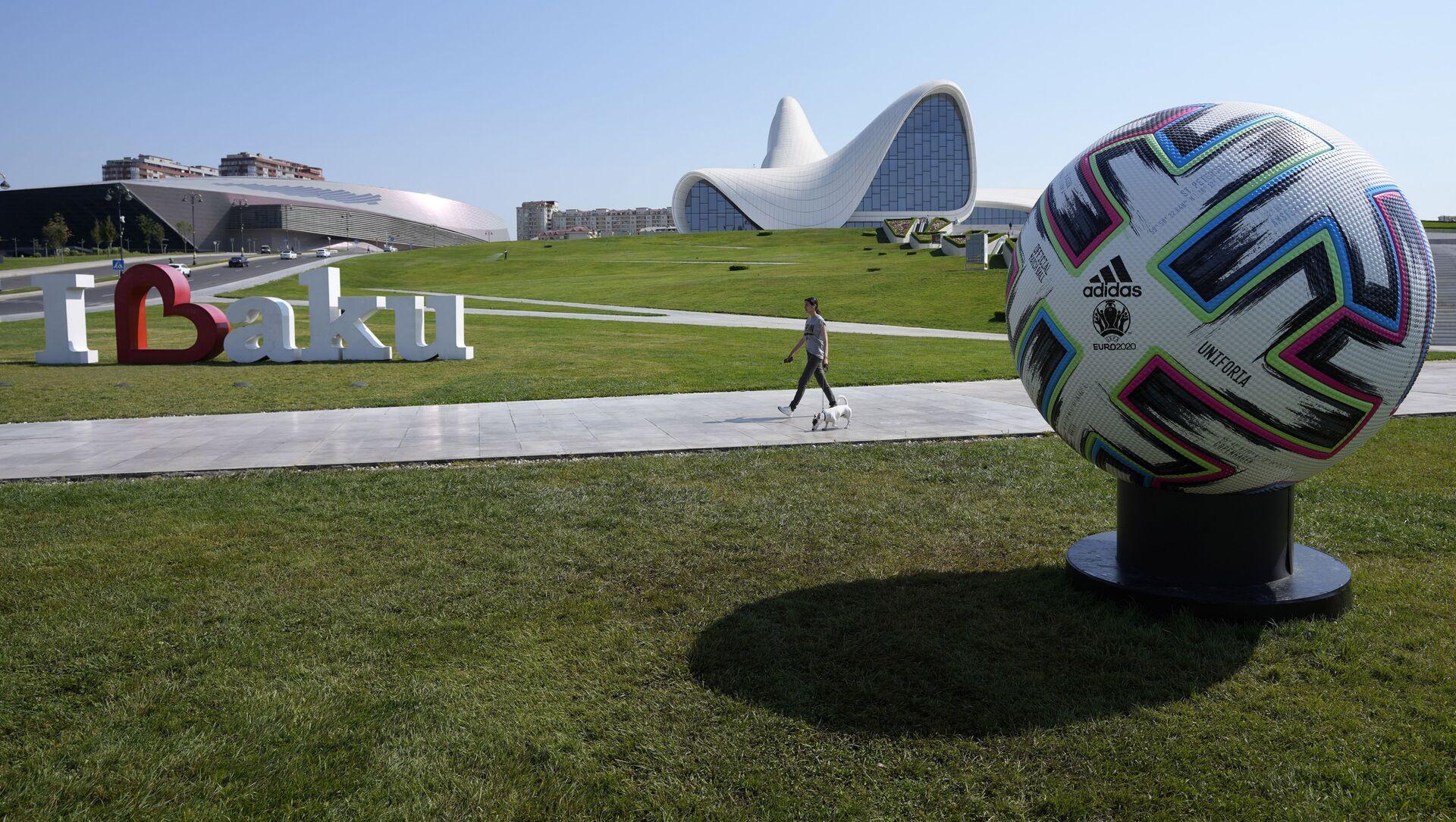 Мужчина проходит рядом с официальным мячом, чемпионата Европы по футболу, фото из архива - Sputnik Азербайджан, 1920, 10.06.2021
