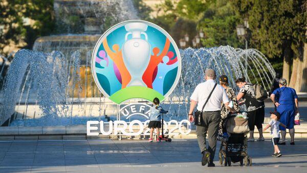 Люди проходит рядом с логтипом, чемпионата Европы по футболу, фото из архива  - Sputnik Azərbaycan