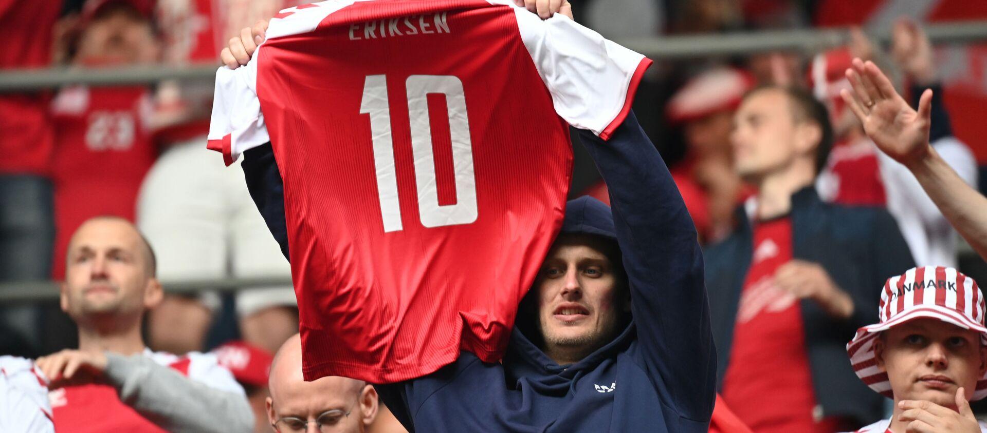 Болельщик сборной Дании держит футболку с номером Кристиана Эриксена - Sputnik Азербайджан, 1920, 13.06.2021
