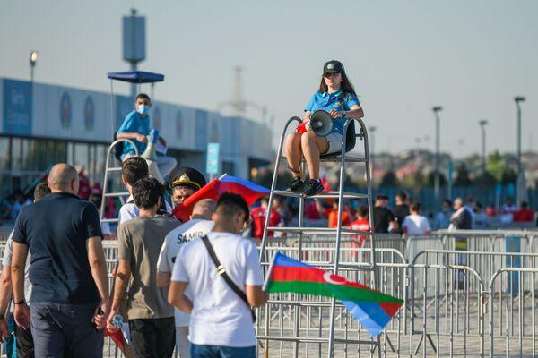 Стюард с громкоговорителем показывает дорогу болельщикам перед Бакинским олимпийским стадионом - Sputnik Азербайджан