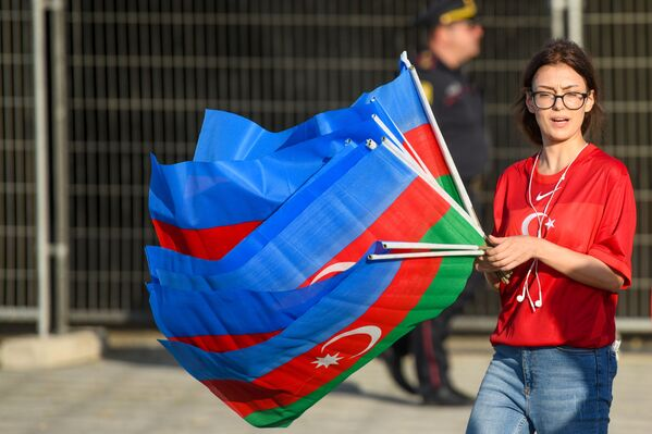Девушка с флагами Азербайджана рядом с Бакинским олимпийским стадионом перед началам матча второго тура группового этапа ЕВРО-2020 Турция-Уэльс - Sputnik Азербайджан