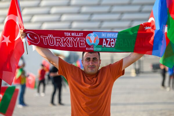 Мужчина с флагами Азербайджана и Турции рядом с Бакинским олимпийским стадионом перед началам матча второго тура группового этапа ЕВРО-2020 Турция-Уэльс - Sputnik Азербайджан
