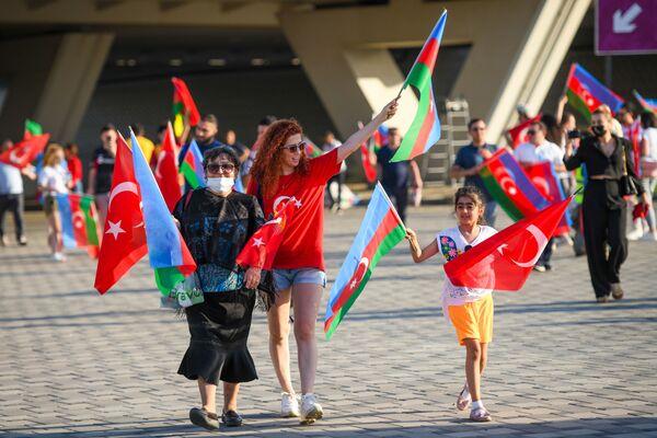 Люди с флагами Азербайджана и Турции рядом с Бакинским олимпийским стадионом перед началам матча второго тура группового этапа ЕВРО-2020 Турция-Уэльс - Sputnik Азербайджан