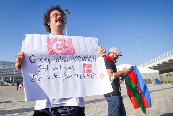 Мужчина с плакатом в поддержку датского футболиста Эриксена  рядом с Бакинским олимпийским стадионом.  - Sputnik Азербайджан