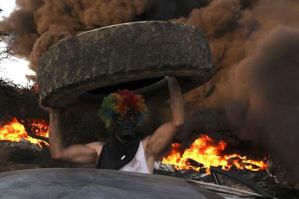 Палестинцы сжигают шины на демонстрации против расширения еврейского поселения Эвиатар на землях деревни Бейта на Западном берегу реки Иордан - Sputnik Азербайджан