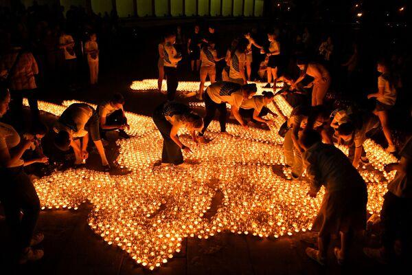 Участники акции Свеча памяти зажигают свечи перед Музеем Победы в Москве - Sputnik Азербайджан